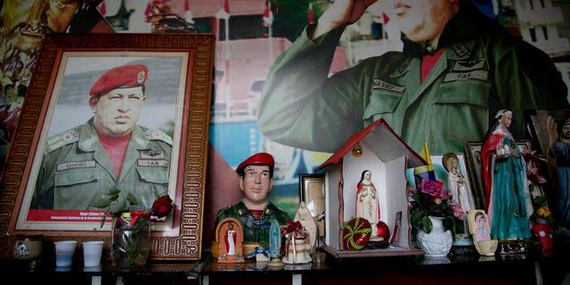 Images of Venezuela's late President Hugo Chavez are surrounded by religious iconography inside a small chapel in the 23 de Enero neighborhood of Caracas, Venezuela, Saturday, March 2, 2019. (AP Photo/Eduardo Verdugo)
