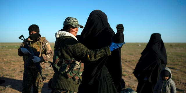 In this March 1 file file, a woman is recovered by an American-assisted Syrian democratic force (SDF) fighter in a foreclosure area after being evacuated from the last territory held by Islamic state militants, in the desert outside Baghouz, Syria.