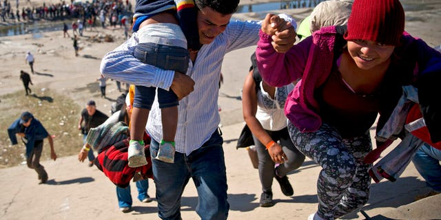 FILE - In this Nov. 25, 2018 file photo, migrants walk up a riverbank at the Mexico-U.S. border after getting past a line of Mexican police at the Chaparral border crossing in Tijuana, Mexico, as they try to reach the U.S. (AP Photo/Ramon Espinosa, File)