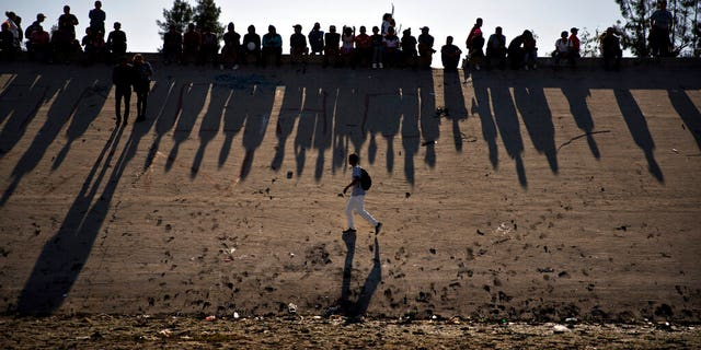 FILE - This Nov. 25, 2018 file photo shows migrants near the Chaparral border crossing watch clashes with U.S. border agents, seen from Tijuana, Mexico. A San Diego TV station says the U.S. government ran an operation to screen journalists, activists and others while investigating last year's migrant caravan from Mexico. KNSD-TV says documents leaked by a Homeland Security source show a January database listing at least 10 journalists, seven of them U.S. citizens, as warranting secondary screening at U.S. points of entry. (AP Photo/Ramon Espinosa, File)
