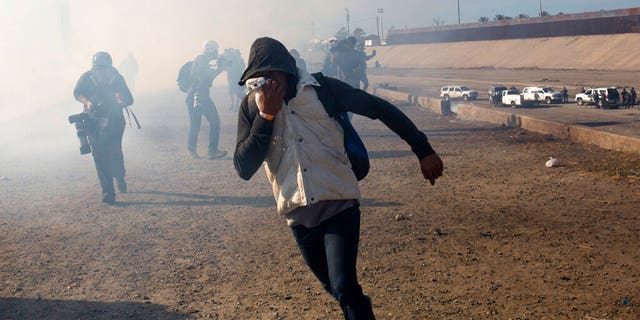 FILE - In this Nov. 25, 2018 file photo, a migrant runs from tear gas launched by U.S. agents, amid members of the press covering the Mexico-U.S. border, after a group of migrants got past Mexican police at the Chaparral crossing in Tijuana, Mexico. (AP Photo/Rodrigo Abd, File)