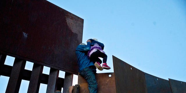 FILE - In this Dec. 2, 2018 file photo, a Honduran migrant helps a young girl cross to the American side of the border wall, in Tijuana, Mexico. (AP Photo/Ramon Espinosa, File)