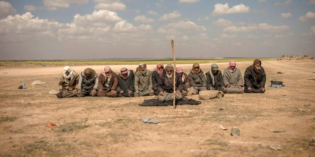In this Wednesday photo, men pray at a reception area for people evacuated from the last shred of territory held by Islamic State militants, outside Baghouz, Syria.