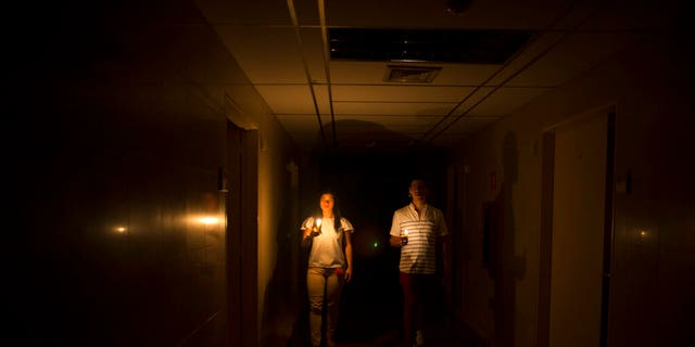 Relatives of a patient walk in the darkened hall of a clinic with a candle lighting the way, during a power outage in Caracas.