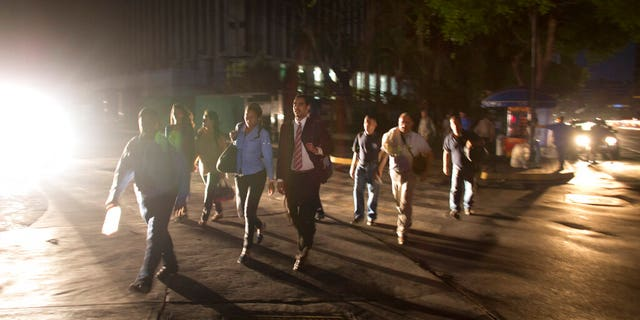 People walk on a dark street during a power outage in Caracas, Venezuela, Thursday, March 7, 2019. A power outage left much of Venezuela in the dark early Thursday evening in what appeared to be one of the largest blackouts yet in a country where power failures have become increasingly common.