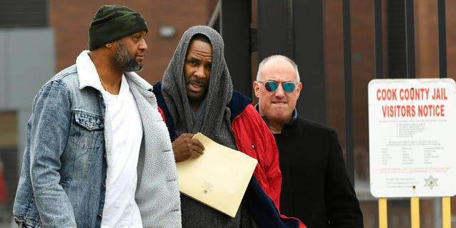 Singer R. Kelly, center, walks with his attorney Steve Greenberg, right, and an unidentified man who gave him a ride after being released from Cook County Jail, March 9, 2019, in Chicago. Kelly walked out of jail after a $161,000 child support payment was made on his behalf.