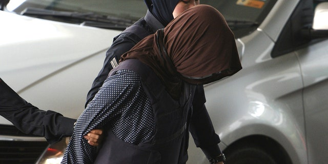 Vietnamese Doan Thi Huong, foreground, is escorted by police as she arrives at Shah Alam High Court in Shah Alam, Malaysia, Monday, March 11, 2019. The trial of two Southeast Asian women charged with murdering Kim Jong Nam, North Korean leader's half brother, resumed Monday after months of delay, with the Vietnamese suspect taking the stand to begin her defense. (AP Photo/Yam G-Jun)
