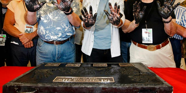 FILE: Don Randi, from left, Glen Campbell and Hal Blaine, representing session musicians known as The Wrecking Crew, hold up their hands after placing them in the cement following the induction ceremony for Hollywood's RockWalk in Los Angeles.