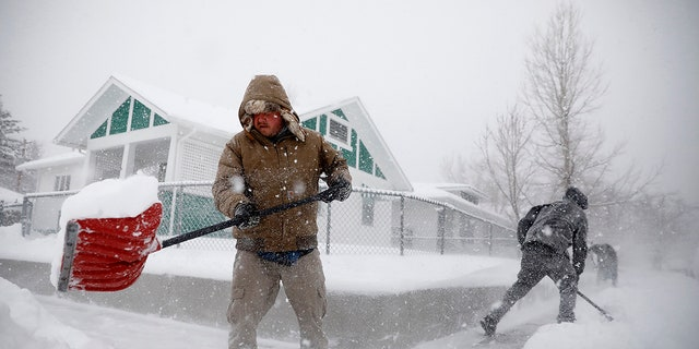 Martin Thompson clears snow from the sidewalk Wednesday, March 13, 2019 during a winter storm in Casper, Wyo. The storm brought blizzard conditions to parts of Colorado, Wyoming, Montana, Nebraska and South Dakota. (Josh Galemore/The Casper Star-Tribune via AP)