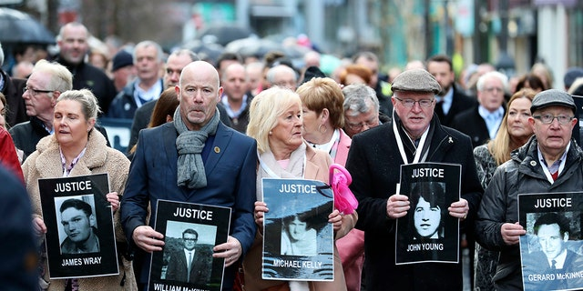 Families hold photographs of the victims of Bloody Sunday and march through the Bogside in Londonderry, Northern Ireland, Thursday, March 14, 2019.