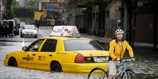 FILE - In this Aug. 28, 2011 file photo, a bicyclist makes his way past a stranded taxi on a flooded New York City street as Tropical Storm Irene passes through the city.  (AP Photo/Peter Morgan, File)