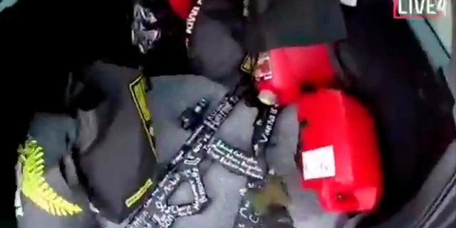 Dans ce cadre de la vidéo diffusée en direct le vendredi 15 mars 2019, un suspect tend la main vers une arme l'arrière de sa voiture avant les fusillades dans la mosquée de Christchurch, en Nouvelle-Zélande. (Associated Press)