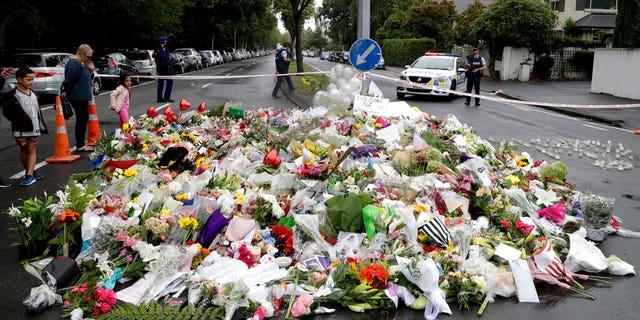 Похмурі поклали квіти на імпровізований меморіал, розташований біля мечеті Масджид Аль Нур в Крайстчерчі, Нова Зеландія, у неділю 17 March 2019, де відбулося одне з двох масштабних зйомок.