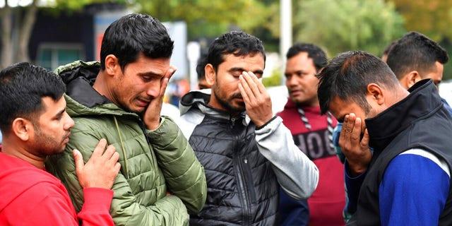 Друзі зниклого чоловіка плачуть перед центром притулку в Крайстчерчі.
