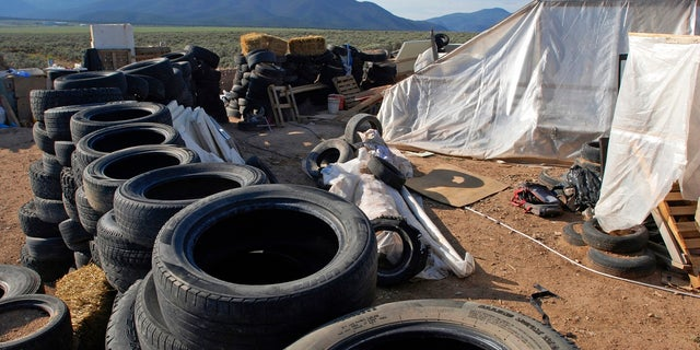 FILE: A makeshift living compound in Amalia, N.M., Aug. 10, 2018. Five former residents of a New Mexico compound where authorities found 11 hungry children and a dead 3-year-old boy are due in federal court on terrorism-related charges.