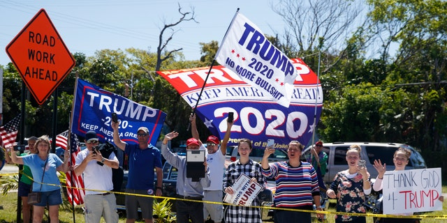 People with signs supporting President Donald Trump are seen from the media van in the motorcade accompanying the president in West Palm Beach, Fla., Friday, March 22, 2019, en route to Mar-a-Lago in Palm Beach, Fla. (AP Photo/Carolyn Kaster)