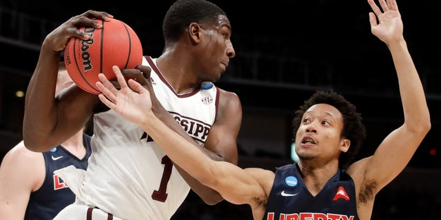 Mississippi State forward Reggie Perry, left, vies for a rebound with Liberty guard Darius McGhee during the first half of a first round men's college basketball game in the NCAA Tournament Friday, March 22, 2019, in San Jose, Calif. (AP Photo/Jeff Chiu)