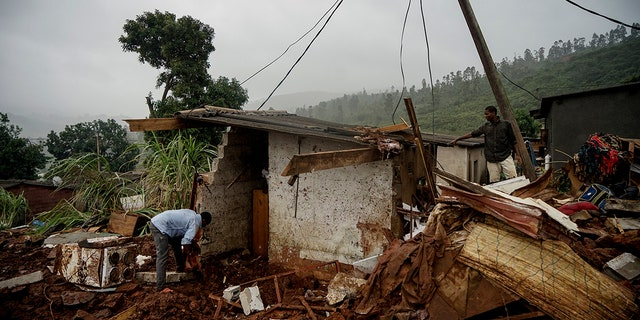 Men search to salvage what they can from a house which was damaged by Cyclone Idai in Chimanimani, Zimbabwe, Saturday, March 23, 2019 after Cyclone Idai caused floods that swept through Mozambique, Zimbabwe and Malawi. A second week has begun of efforts to find and help some tens of thousands of people in devastated parts of southern Africa, with some hundreds dead and an unknown number of people still missing.(AP Photo/KB Mpofu)