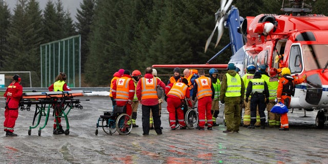 Passengers are helped from a rescue helicopter in Fraena, Norway, Sunday.