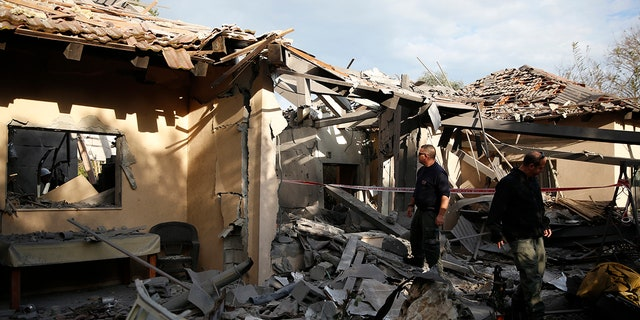 Police officers inspect the damage to a house hit by a rocket in Mishmeret, central Israel, Monday, March 25, 2019. An early morning rocket from the Gaza Strip struck a house in central Israel on Monday, wounding six people, including one moderately, an Israeli rescue service said, in an eruption of violence that could set off another round of violence shortly before the Israeli election. (AP Photo/Ariel Schalit)