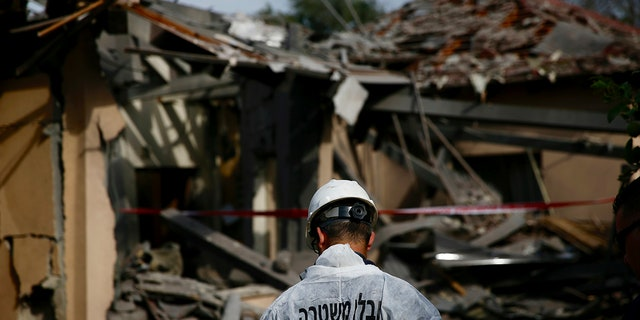 An Israeli police officer inspects the damage to a house hit by a rocket in Mishmeret, central Israel, on Monday, March 25, 2019. Early morning A rocket from the Gaza Strip hit a house in central Israel on Monday, injuring several people, including a moderate, Israeli rescue service said. An outbreak of violence that could trigger another round of violence just before the Israeli elections. (AP Photo / Ariel Schalit)