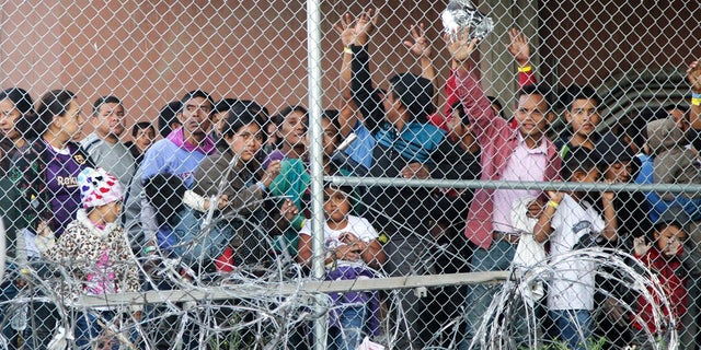 Central American migrants wait for food in El Paso, Texas on Wednesday in a pen erected by U.S. Customs and Border Protection to process a surge of migrant families and unaccompanied minors. (AP Photo/Cedar Attanasio)
