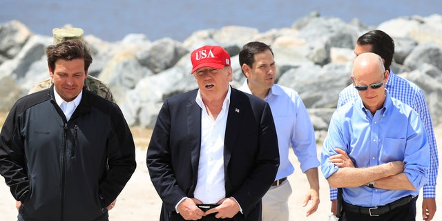 President Donald Trump walks with, from left, Florida Gov. Ron DeSantis, Sen. Marco Rubio, R-Fla., and Sen. Rick Scott, R-Fla., during a visit to Lake Okeechobee and Herbert Hoover Dike at Canal Point, Fla., Friday, March 29, 2019. (AP Photo/Manuel Balce Ceneta)