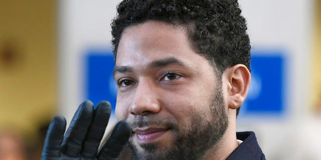 Actor Jussie Smollett smiles and waves to supporters before leaving Cook County (Ill.)Court after his charges were dropped in Chicago. (Associated Press)