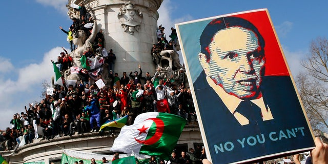 Protesters wave Algerian flags and hold posters opposing Algeria President Abdelaziz Bouteflika's bid for a fifth term in Paris Sunday