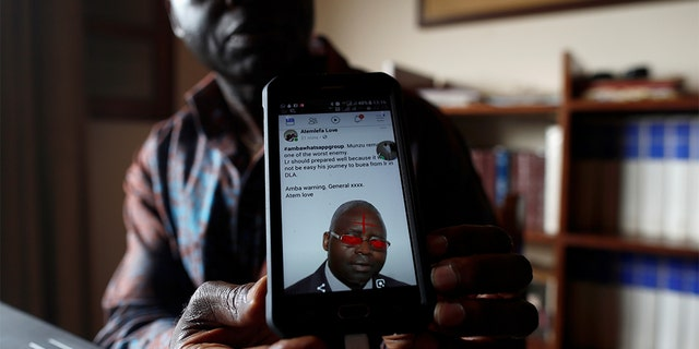Simon Munzu, a former UN official, who is campaigning for peace in the Anglophone regions of Cameroon, shows a threat message posted against him on social media by separatists during an interview with Reuters in Yaounde, Cameroon.