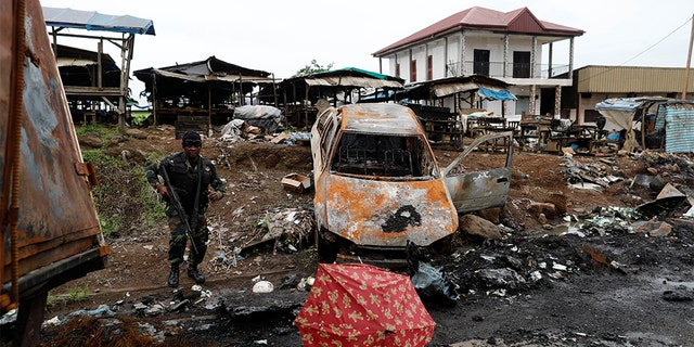 A Cameroonian elite Rapid Intervention Battalion (BIR) member walks past a burnt car while patrolling in the city of Buea in the anglophone southwest region, Cameroon October 4, 2018. Picture taken October 4, 2018.
