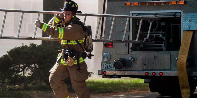 Berwick Fire Capt. Joel Barnes pulling a ladder on the scene of a June 2017 structure fire in Somersworth N.H. (Erin Thomas via AP, File)