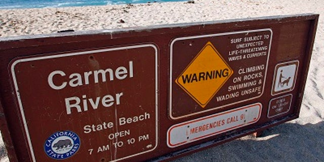 A warning sign shows the dangerous conditions near the Monastery Beach area of Carmel River State Beach in Carmel, Calif.