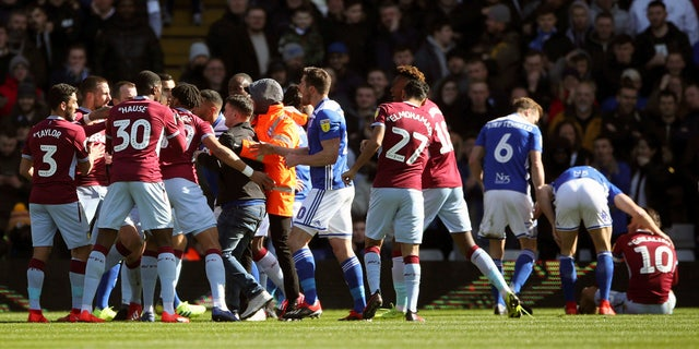 A fan was removed after attacking Aston Villa's Jack Grealish, right, on the pitch during the Sky Bet Championship soccer match at St Andrew's Trillion Trophy Stadium, Birmingham, England, onSunday. (Nick Potts/PA via AP)