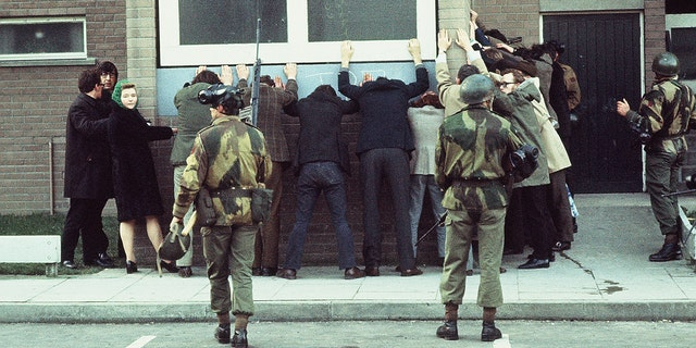 British troops arrest civilians on Rossville St, Londonderry, during a civil rights march. The day went on to become known as Bloody Sunday as British paratroopers shot dead 14 civilians.