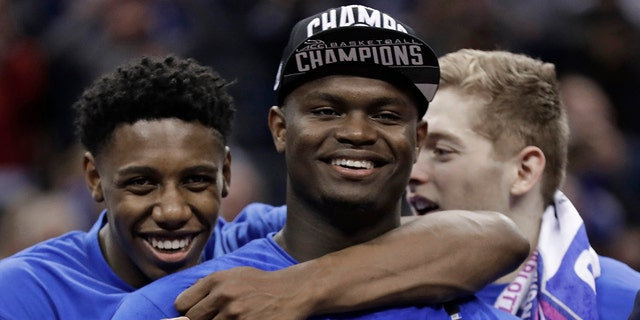 Duke's RJ Barrett, left, hugs Zion Williamson after Duke defeated Florida State in the NCAA college basketball championship game of the Atlantic Coast Conference tournament in Charlotte, N.C., Saturday, March 16, 2019.