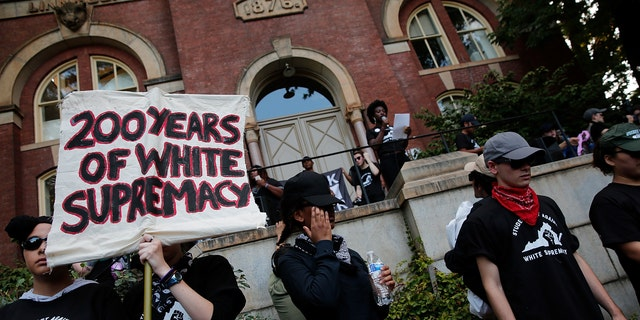 Protesters with the group Students Act Against White Supremacy speak on the campus of the University of Virginia during an event marking the one year anniversary of a deadly clash between white supremacists and counter-protesters Aug. 11, 2018, in Charlottesville, Va.