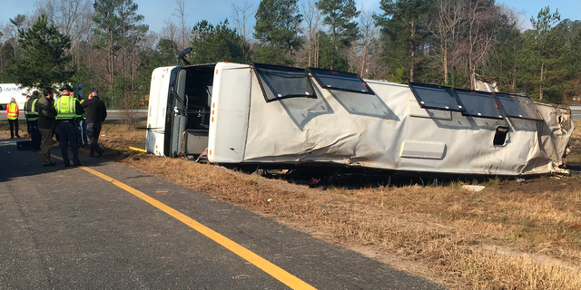 This photo provided by Virginia State Police emergency responders at the scene after a charter bus overturned on an Interstate 95 exit near Kingwood, Va., Tuesday. (Virginia State Police via AP)