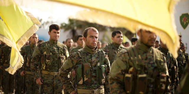 U.S.-backed Syrian Democratic Forces (SDF) stand in formation at a ceremony to mark their defeat of Islamic State militants in Baghouz, at al-Omar Oil Field base, Syria, Saturday, March 23, 2019. (AP Photo/Maya Alleruzzo)