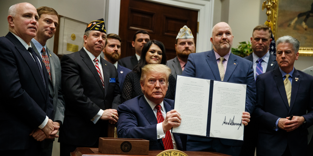 """President Trump displays his signed executive order establishing a """"National Roadmap to Empower Veterans and End Veteran Suicide"""" in March 2019. (AP Photo/ Evan Vucci)"""