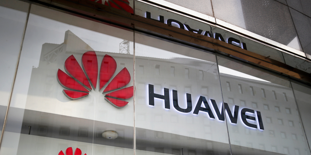 FILE - In this Jan. 29, 2019, file photo, the logos of Huawei are displayed at its retail shop window reflecting the Ministry of Foreign Affairs office in Beijing.  (AP Photo/Andy Wong, File)