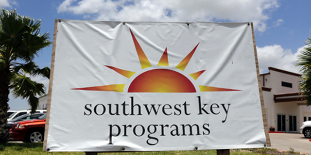 FILE - This June 20, 2014, file photo shows a Southwest Key program sign in Brownsville, Texas. Authorities in Arizona say workers who were seen on video dragging and shoving immigrant children being held at a privately run shelter won't face charges. The Maricopa County Attorney's Office said Friday, March 29, 2019 that there's no reasonable likelihood of proving the workers at a Southwest Key facility committed a crime. (AP Photo/Eric Gay, File)