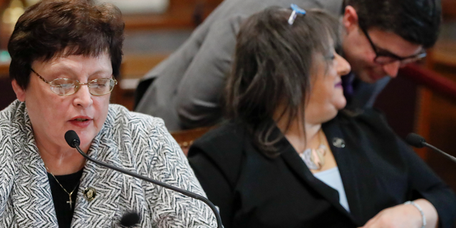 Pittsburgh City Council member Darlene Harris, left, speaks on a vote on gun-control legislation as fellow council members Corey O'Connor, right, and Theresa Smith, center, have a discussion, during a City Council meeting, Wednesday, March 27, 2019, in Pittsburgh. The bill passed as members voted 6-3 to pass tentative approval to the gun-control legislation introduced in the wake of the synagogue massacre last October. The legislation would place restrictions on military-style assault weapons like the AR-15 rifle that authorities say was used in the attack that killed 11 and wounded seven. A final vote will take place next week. Harris, Smith and Anthony Coghill voted against the bill O'Connor co-sponsored. (AP Photo/Keith Srakocic)