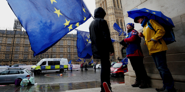 Remain supporters shelter from the wind and rain across the street from parliament in London, Thursday, Feb. 28, 2019. (Jonathan Brady/PA via AP)
