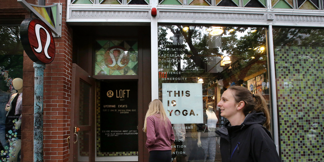 FILE- In this June 5, 2017, file photo, people walk near an entrance to a Lululemon Athletica store on Newbury Street in Boston. Lululemon Athletica Inc. reports earnings on Wednesday, March 27, 2019. (AP Photo/Steven Senne, File)
