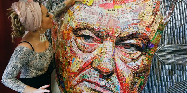 Ukrainian artist Dasha Marchenko adds a chocolate wrapper to her portrait of Ukraine's President and chocolate tycoon Petro Poroshenko at her studio in Kiev, Ukraine, Thursday, March 28, 2019. (AP Photo/Efrem Lukatsky)