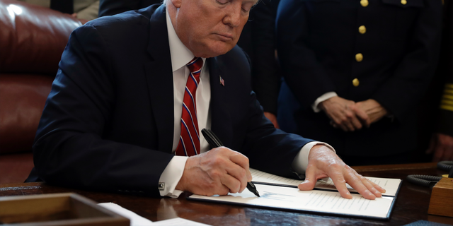 President Donald Trump signs the first veto of his presidency in the Oval Office of the White House, Friday, March 15, 2019, in Washington. Trump issued the first veto, overruling Congress to protect his emergency declaration for border wall funding. (AP Photo/Evan Vucci)