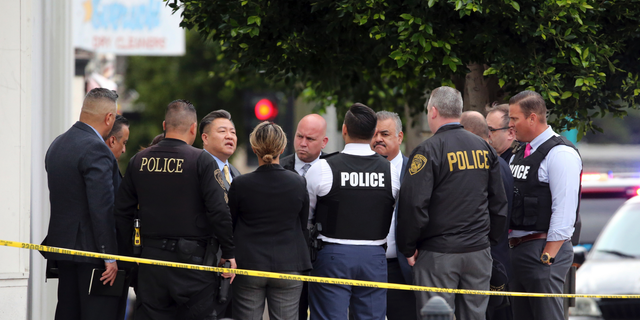 Investigators confer just down the street from the Church of Scientology after a shooting wounded two police officersand killed a sword-wielding suspect in Inglewood, Calif., on Wednesday. (Associated Press)