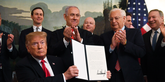 President Donald Trump holds up a signed proclamation recognizing Israel's sovereignty over the Golan Heights, as Israeli Prime Minister Benjamin Netanyahu looks on in the Diplomatic Reception Room of the White House in Washington, Monday, March 25, 2019. (AP Photo/Susan Walsh)