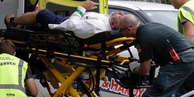 Ambulance staff take a man from outside a mosque in central Christchurch New Zealand Friday